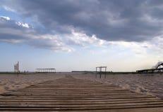 Houten weg aan het overzees door het zand en de bewolkte hemel royalty-vrije stock afbeeldingen