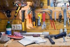 Houten werkbank op workshop Partij van verschillende hulpmiddelen voor de diy en reparatiewerken Houten slordige lijst met notiti stock fotografie