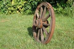 Houten wiel op een achtergrond van groen gras Stock Foto's