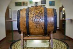 Houten wijnvat met druivenpatroon in het midden die op houten tribune op een lijst liggen stock afbeeldingen