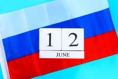Houten witte kalender met de datum van 12 Juni tegen de achtergrond van de vlag van Rusland De Dag van Rusland Royalty-vrije Stock Foto