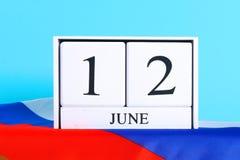 Houten witte kalender met de datum van 12 Juni tegen de achtergrond van de vlag van Rusland De Dag van Rusland Stock Afbeeldingen