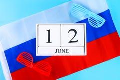 Houten witte kalender met de datum van 12 Juni tegen de achtergrond van de vlag van Rusland De Dag van Rusland Royalty-vrije Stock Foto's