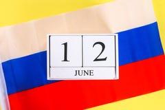 Houten witte kalender met de datum van 12 Juni tegen de achtergrond van de vlag van Rusland De Dag van Rusland Stock Foto