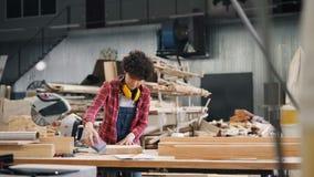 Houten workshoparbeider het oppoetsen stuk van hout met schurend blok in werkplaats stock footage