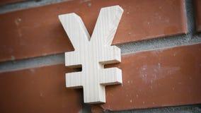Houten Yensymbool op bakstenen muurachtergrond Royalty-vrije Stock Foto's