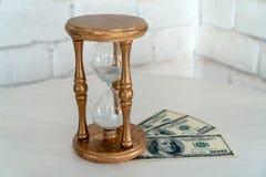Houten Zandloper en geld op een witte achtergrond Het concept tijd is geld royalty-vrije stock fotografie