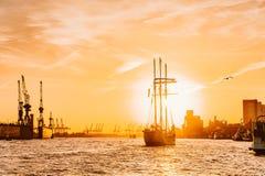 Houten zeilboot die naar dramatische zonsondergang varen die met nieuw reisavontuur met vliegende vogel beginnen stock foto's