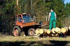 Houthakkers die tractor met behulp van Stock Foto's
