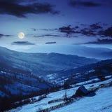 Houtschuurtje op de helling in de winterbergen bij nacht Stock Foto's