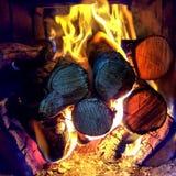 Houtskool en houtlogboekenbrandwond met vlamuitbarsting in open schoorsteenopen haard stock fotografie