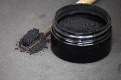 Houtskool op een tandenborstel om tanden te witten stock afbeelding