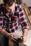 houtverwerking Zekere jonge mannelijke timmerman die met hout werken Stock Foto's