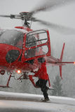 Hover Entry. A rescue worker climbs into a helicopter while it hovers a few feet off the ground Royalty Free Stock Photography