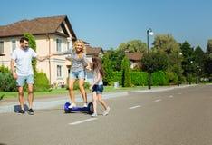Hoverboard de soutien d'équitation de femme de famille affectueuse Images stock
