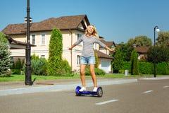 Hoverboard gai d'équitation de femme et mains de propagation Photos stock