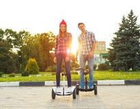 Hoverboard joven del montar a caballo de los pares - vespa eléctrica, EC personal Fotos de archivo libres de regalías