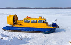 Hovercraft on the bank of frozen river Stock Photos