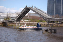 Hovercraft under bridge. Hovercraft trials on River Clyde Glasgow. The Millenium Bridge has been opened to let the craft pass through.  If the trial is Royalty Free Stock Photos