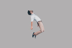 Hovering in air. Mid-air shot of handsome young man jumping and gesturing against background Royalty Free Stock Image