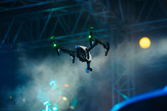Hovering drone with camera on stage. Professional drone with video camera hanging in the air during show stock image