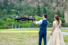 Hovering drone shooting young couple on their wedding in nature