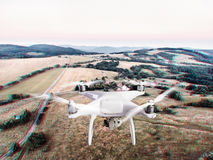 Hovering drone taking pictures of green grasslands, houses and f Stock Photo