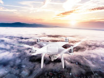Hovering drone taking pictures of town covered by mist, sunrise Royalty Free Stock Image