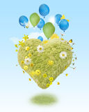 Hovering green heart. A harmonic composition of lightness, in form of a green heart, hovering with balloons and small toy wind wheels with a soft light in the Royalty Free Stock Photo
