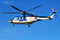 Hovering helicopter on blue sky. Small  passenger helicopter hovering on blue sky Stock Photo