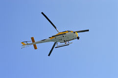 Hovering Helicopter. A helicopter hovers overhead with the passengers feet over the side Stock Image