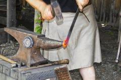Hovslagare i en arbetskilt som dunkar ett glödhett stycke av metall med en hammare på ett städ - händer i rörelse arkivbild