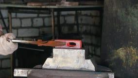 Hovslagare på arbete med den elektriska hammaren på städet, glödhett stål, hantverk stock video