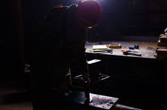 Hovslagare som arbetar i en smedja i panelljus Gammalt kompass och rep på burlap arkivbild