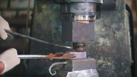 Hovslagare som arbetar med den elektriska hammaren på städet, arbetande man som gör hål i glödhett stål, hantverk lager videofilmer