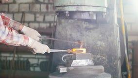 Hovslagare som arbetar med den elektriska hammaren på städet som gör hålet i glödhett stål, hantverk stock video