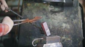 Hovslagare som arbetar med den elektriska hammaren på städet, man som gör hål i varmt stål, hantverk stock video