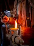 Hovslagare som böjer en varm metallstång Royaltyfria Foton
