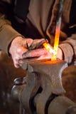 Hovslagare som böjer en varm metallstång Arkivbild