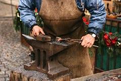 Hovslagarearbetemetall med en hammare på städet i smedjan Arkivbild