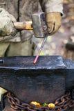 Hovslagaren förfalskar den varma stålstången med släggan arkivbilder
