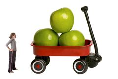 How 'bout them Apples. Young Teen Girl looking up at a large wagon full of granny smith apples stock images
