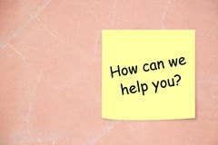 How can we help you note. On yellow note with pink wall Stock Image