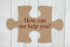 How can we help you text on a cardboard puzzle piece. Getting your questions answered, How can we help you text on a cardboard puzzle piece stock photography
