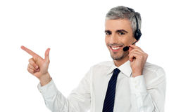 How can I assist you today?. Customer service executive pointing at something Stock Photo
