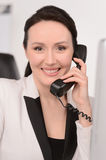 How can I help you? Confident middle-aged businesswoman sitting Stock Image
