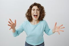 How could you betray my trust. Portrait of desperate miserable woman with curly hair in trendy glasses, bending towards. Camera, shaking palms and yelling at royalty free stock photos