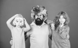 How crazy is your father. Man bearded father and kids girls wear colorful wig violet background. Friendly family wear stock photos
