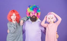 How crazy is your father. Man bearded father and kids girls wear colorful wig violet background. Friendly family wear royalty free stock images