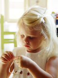 How does this work?. A little girl untying her ribbon Stock Photos